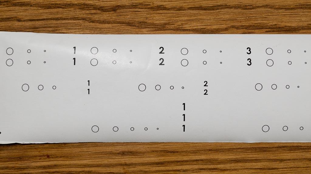 Auf der Rückseite des Fujifilm Acros Neopan befinden sich Markierungen für die Aufnahmeformate 6x6, 6x7 und 6x9 (von oben nach unten). Je kleiner die Kreise im Sichtfenster werden, desto näher ist man an der korrekten Position.